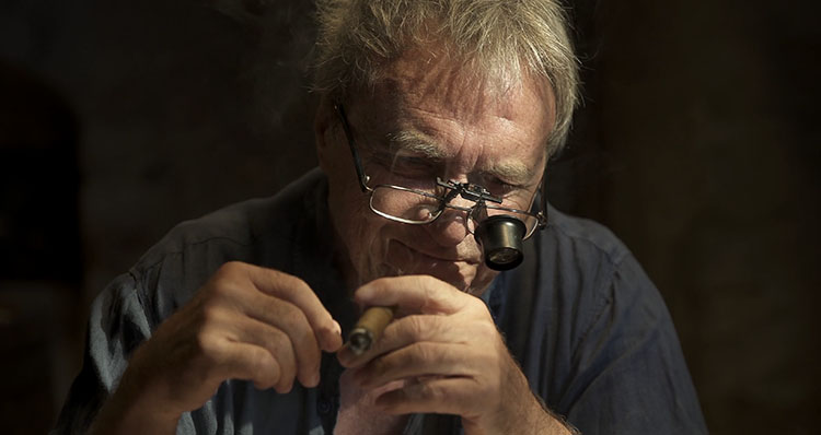 Man sitting in dark cellar smoking cigar